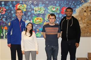 Students stand in front of bulletin board.